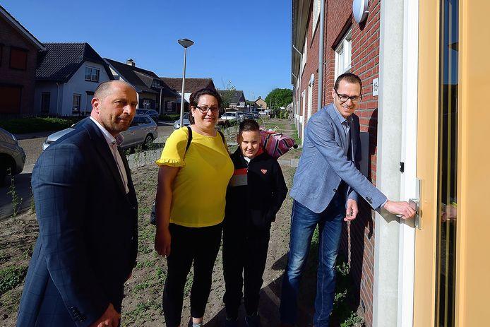 De familie Van Unen krijgt de sleutel van de nieuwe woning aan de Hendrikstraat van Pierre Hobbelen (links) van Thuisvester en van wethouder Martien de Bruijn (rechts).