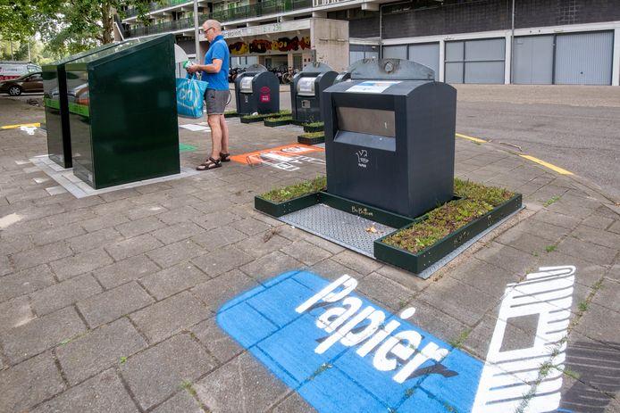 Groene bakken rond de ondergrondse afvalcontainers op het Gelderseplein in Arnhem, alsook aanduidingen op het wegdek van wat waar in moet.