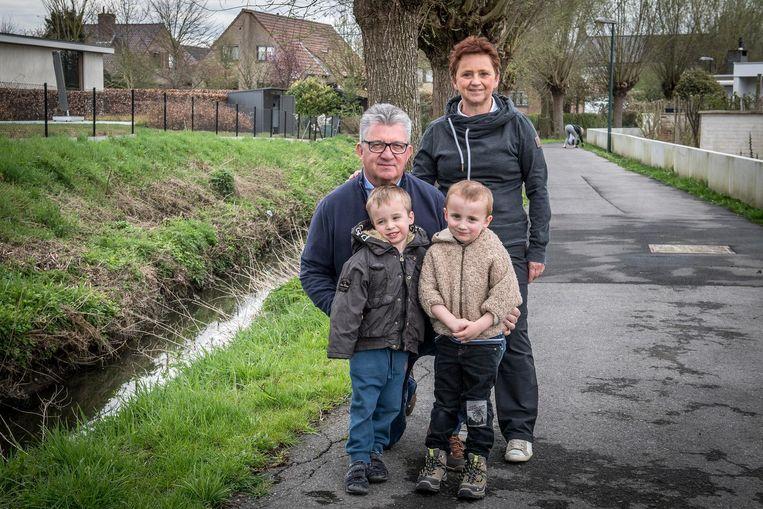Thierry Bouckenooghe van het Wijkcomité met vrouw Hilde en kleinkinderen Sam en Aaron bij de beek.