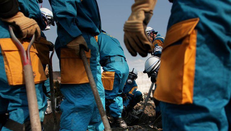 Politie en reddingswerkers doorzoeken de puinhopen van Minamisanriku. Beeld getty