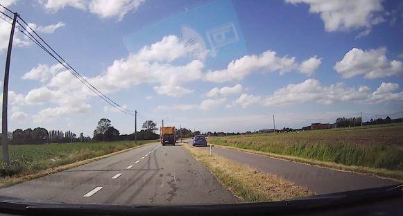 De bestuurder van de blauwe auto is het beu en haalt het landbouwvoertuig in via het gras en het fietspad