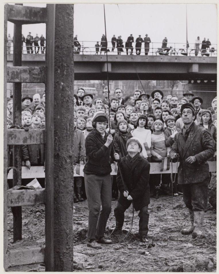 25 november 1964. Twee jeugdige bewoners van de Indische buurt heien de eerste paal voor het te bouwen zwembad Beeld Stadsarchief