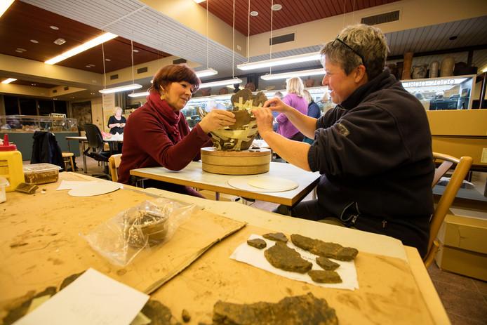 Vrijwilligers van de Arechologische Vereniging Kempen de Peel aan het werk in het Erfgoedhuis in Eindhoven