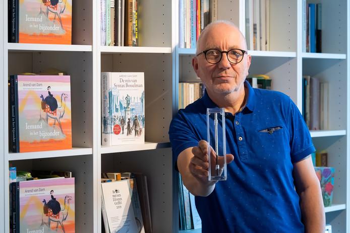 Arend van Dam toont de Zilveren Griffel die hij gewonnen heeft met zijn historisch jeugdboek 'De reis van Syntax Bosselman'.