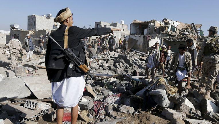 Een man wijst naar de brokstukken die het gevolg zijn van luchtaanvallen nabij het vliegveld in de hoofdstad Sanaa. Beeld reuters