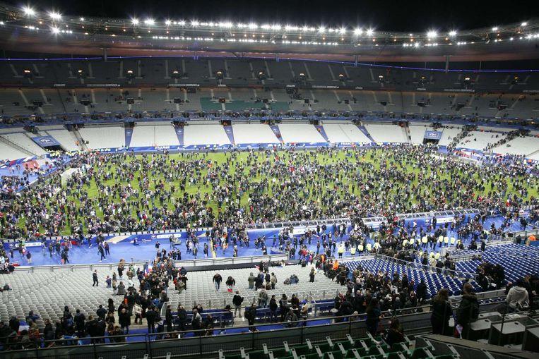 Toeschouwers staan op het veld in het Stade de France. Beeld afp