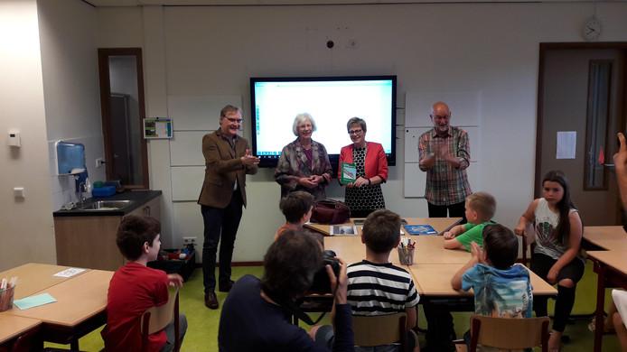 Burgemeester Miranda de Vries heeft zojuist op basisschool De Springplank het boekje gekregen uit handen van schrijfster Ine van den Hoven.