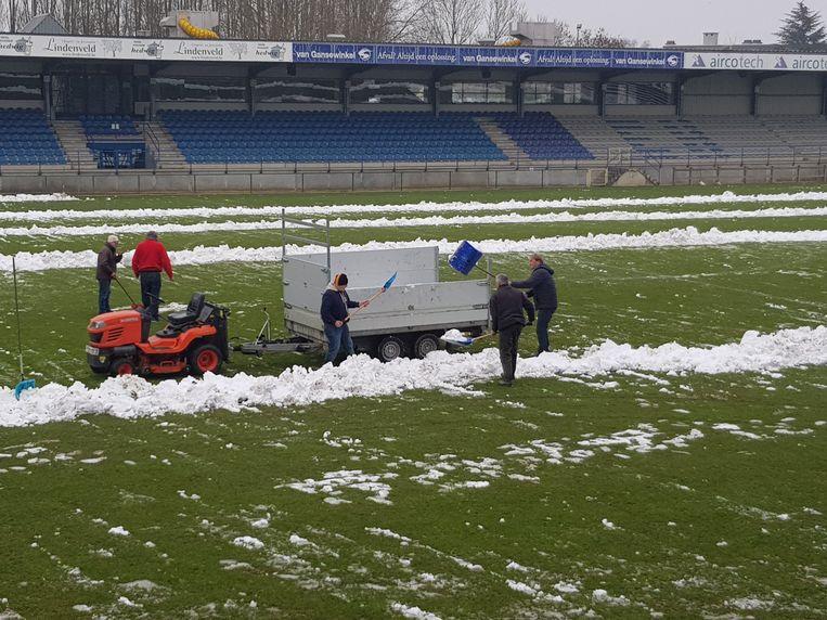 Supporters maken het terrein van FC Dender sneeuwvrij.