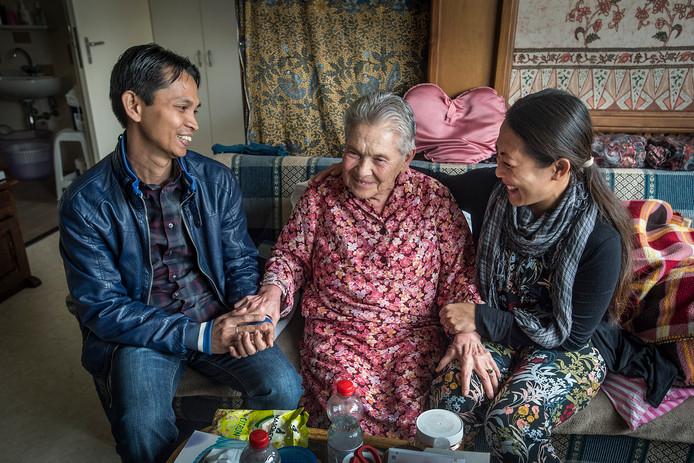 Dini Westerkamp-Wolff (88) geniet in het Bredase Huize Raffy van de hulp van de Indonesische verpleegkundigen Niki Candrawati en Yudi Setiawan. foto Ron Magielse