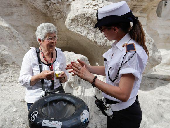 Een politieagente praat met een vrouw die een ijsje eet bij de Trevifontein in Rome, vrijdag 7 juni 2019.