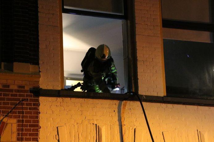 Een brandweerman op de eerste verdieping van het pand aan de Van Karnebeekstraat in Zwolle.
