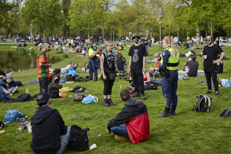 Handhavers wijzen bezoekers van het Vondelpark in Amsterdam erop dat ze zich moeten houden aan de anderhalvemeterregels.  Beeld Getty Images