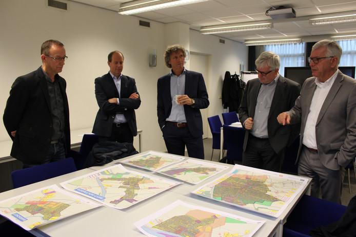 Wethouder Jan van de Wiel (rechst) geeft gedeputeerde Van Merrienboer (naast hem) uitleg over de woningbouwplannen in Hilvarenbeek.
