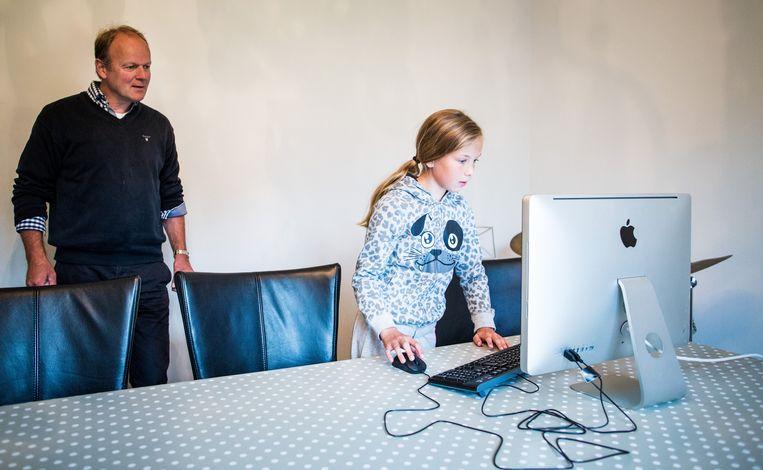 Lotte van der Sluis (11) en haar vader kijken of ze de selectie heeft gehaald. Beeld Van Den Bergh Freek