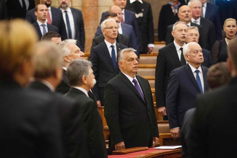 Premier Viktor Orban (midden) zingt het volkslied in het parlement.  Beeld AFP