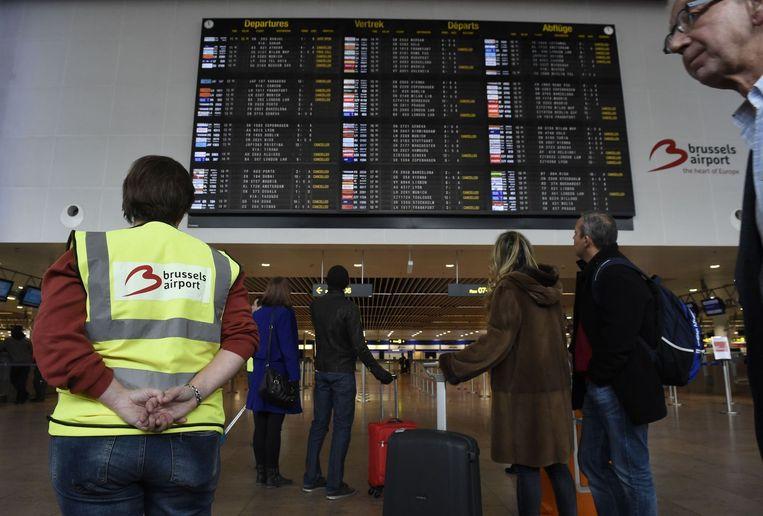Passagiers op het vliegveld in Brussel kijken naar de vertrektijden van vluchten. Beeld null