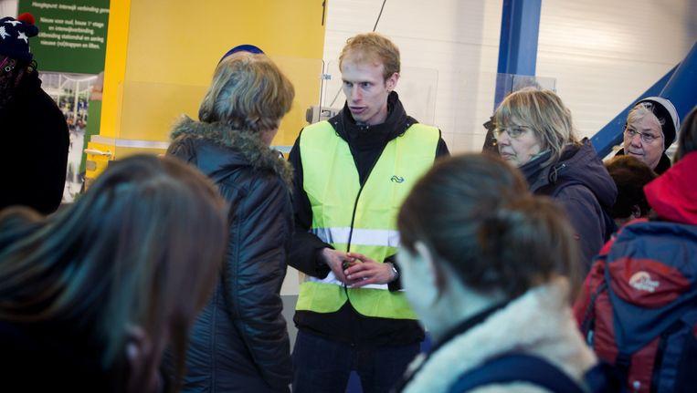 Een NS-medewerker staat gestrande reizigers te woord. Beeld anp