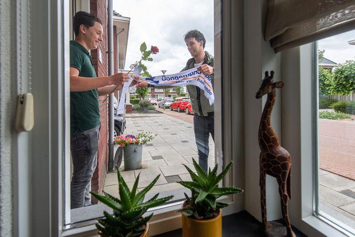 Levi van ERp, mentor van klas MT4B van het Dongemond college in Made gaat langs de geslaagden om de cijferlijst, een roos en een wimpel te brengen. Jannes Peijs neemt de spullen aan.