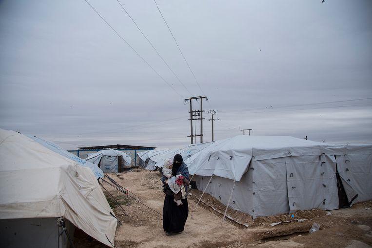 Een vrouw met haar kind tussen tenten in een Syrisch kamp.  Beeld Barcroft Media via Getty Images
