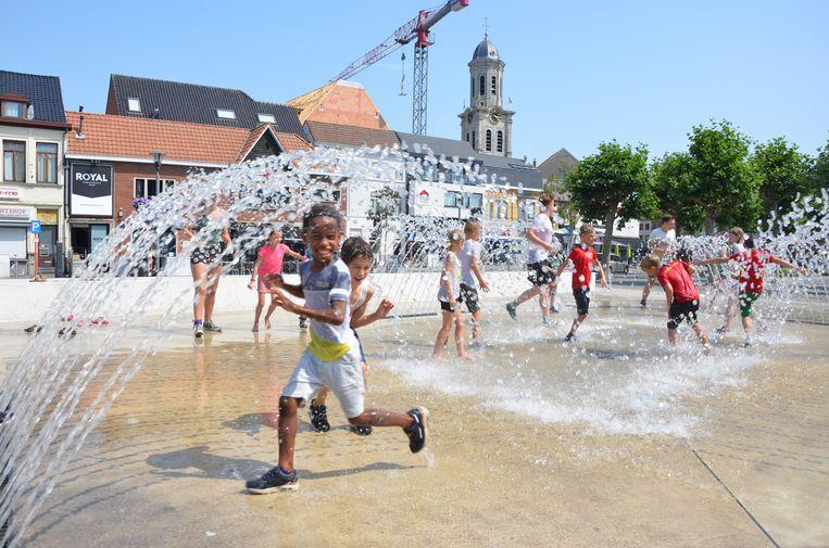 De kinderen van de Chiro uit Wijtschate zoeken verkoeling in de fontein op de Markt van Lokeren.