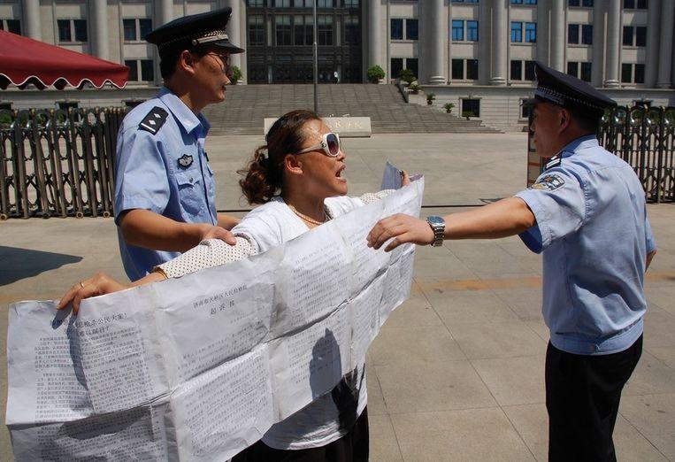 Een aanhangster van Bo Xilai bij de rechtbank in Jinan wordt door de politie weggeduwd. Beeld epa