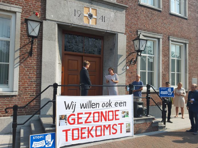Nelly van Oijen overhandigt de 3000 handtekeningen voor de deur van het gemeentehuis aan burgemeester Michiel van Veen.