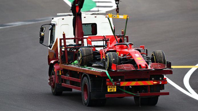 De Ferrari van Sebastian Vettel wordt afgevoerd nadat hij is stilgevallen tijdens de training voor de 107thAnniversary Grand Prix op Silverstone.