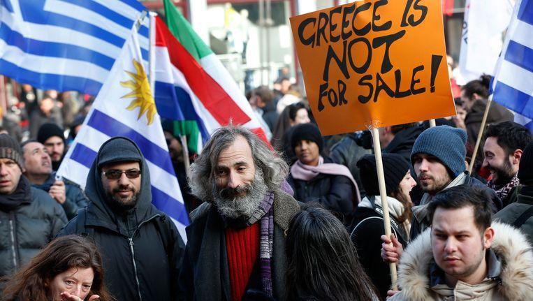 Deelnemers aan een solidariteitsdemonstratie voor de Grieken op de Dam. Ze betuigen hun steun aan de inwoners van Griekenland tijdens de onderhandelingen met de Eurogroep. Beeld ANP