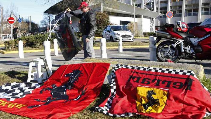 Een fan van Michael Schumacher legt vlaggen van Ferrari neer voor het CHU Nord hospital in Grenoble.