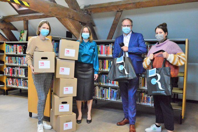 Schepenen Jan Desmeth en An Speeckaert samen met de medwerkers van de bibliotheek in Sint-Pieters-Leeuw die de pakketten samenstellen.