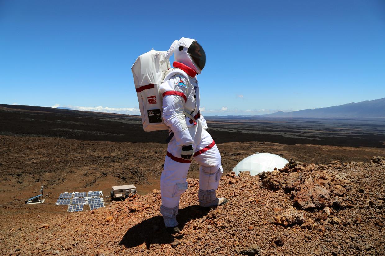Een 'astronaut' bij de HiSEAS-basis op Hawaii, met op de achtergrond de Mauna Loa-vulkaan. Beeld Angelo Vermeulen