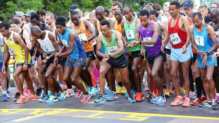 Marathonrenners stellen hun sporthorloge in. Beeld Bob King