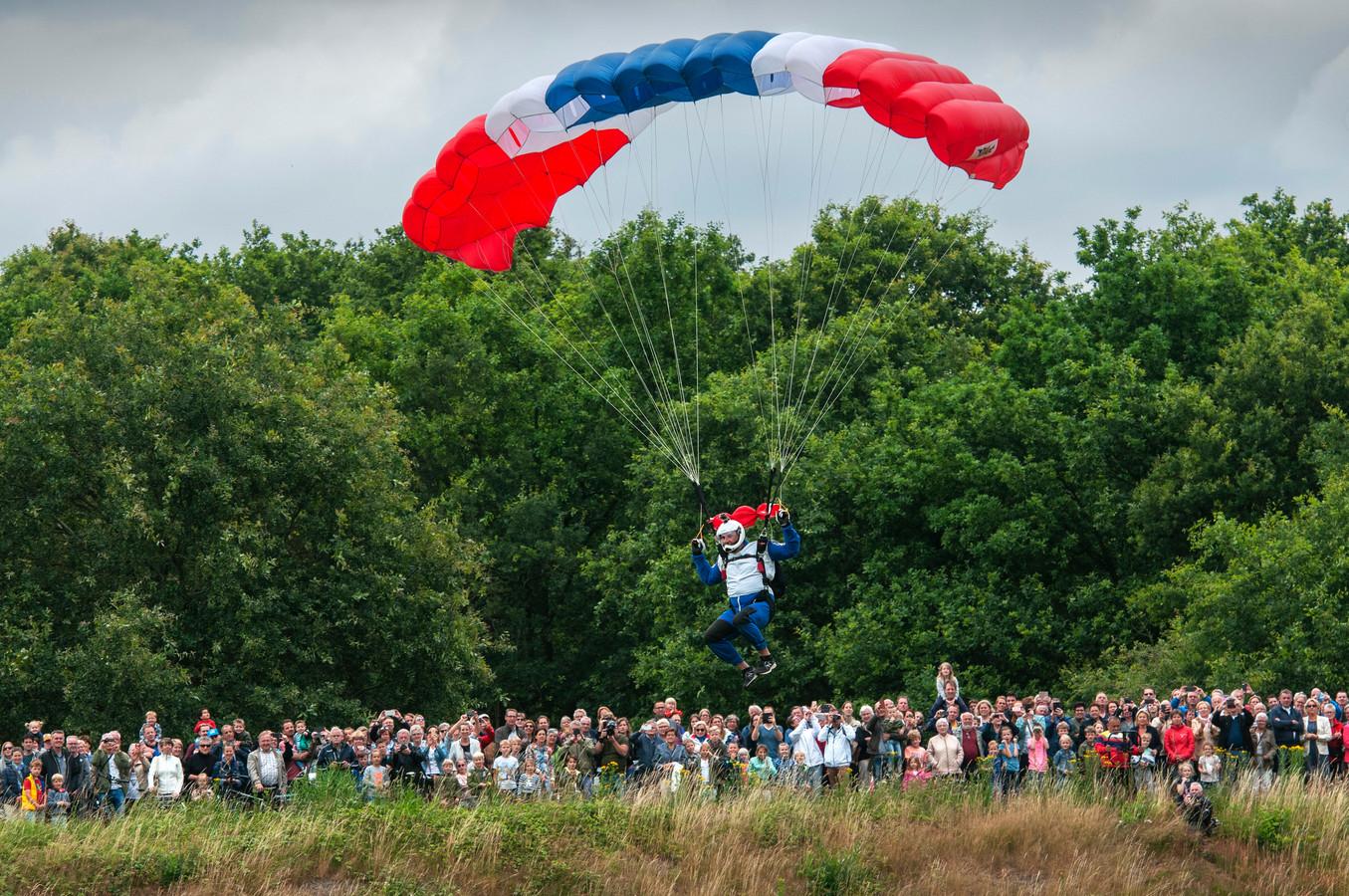 Een parachutist landt in de Gement bij Vught, vlakbij Fort Isabella. Het publiek op de Honderdmorgensedijk kijkt toe..