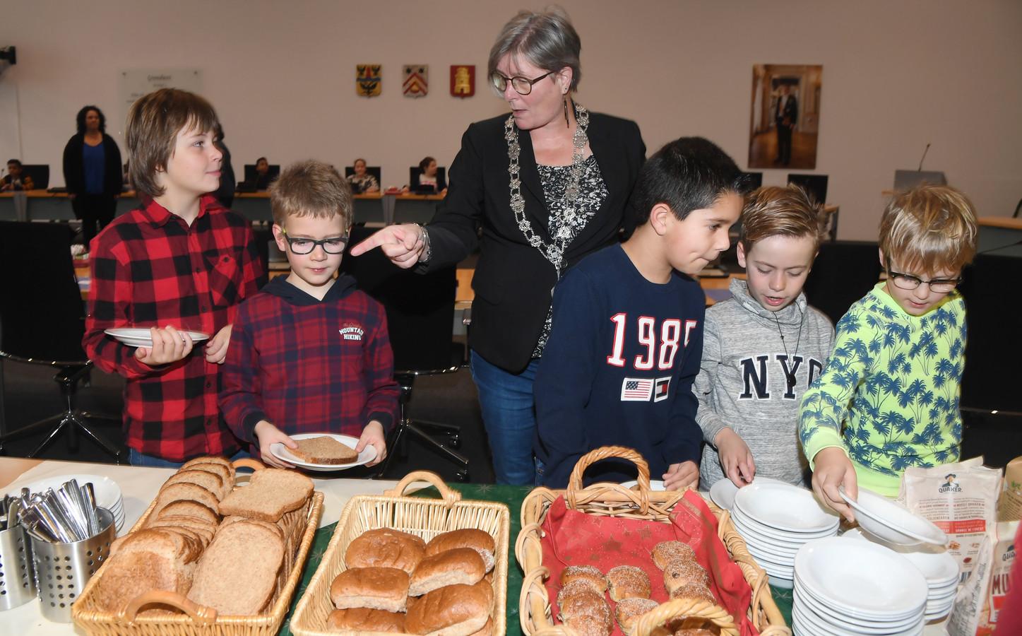 Locoburgemeester Carla Doorn helpt de kinderen van de Cypressenhof met het ontbijt.