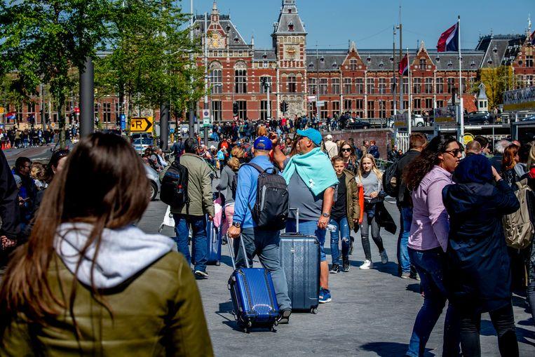 Voorbijgangers met rolkoffers bij het drukke Amsterdam Centraal. Beeld ANP