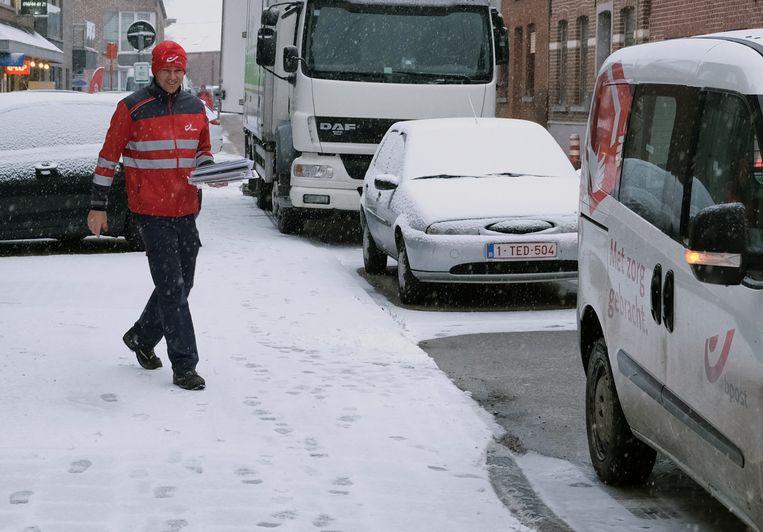 De postbode bewaart de glimlach op deze witte ochtend.