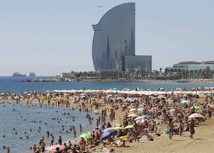 epa05486456 Thousands of holidaymakers enjoy the sunny weather at the Barceloneta beach in Barcelona, Spain, 15 August 2016.  EPA/ANDREU DALMAU