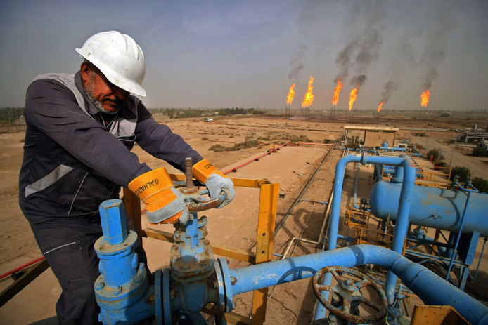 Een technicus draait aan een gaskraan in een olieveld in Irak
