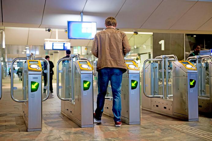 Een reiziger passeert een toelatingspoort op Rotterdam Centraal.