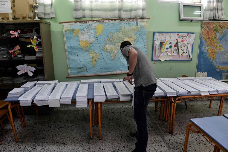 Een man pakt een stembiljet in de Griekse stad Thessaloniki. Beeld AFP
