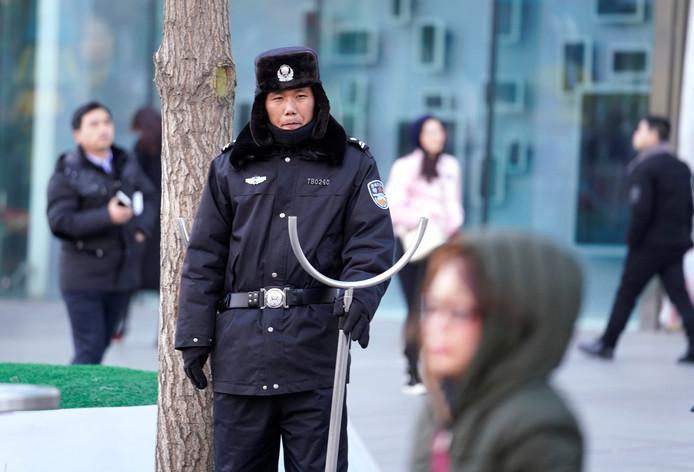 Chinese bewakers patrouilleren met een 'afstandshouder' in de hand, bij het winkelcentrum Joy City in Beijing, nadat een messentrekker actief is geweest en winkelend publiek heeft verwond. Foto Jason Lee