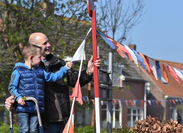 Bestuurslid Johan Cevaal van Oranje Boven en zoon Ronny hingen tijdens een vorige editie van Koningsdag oranjeversierselen op in Ritthem.