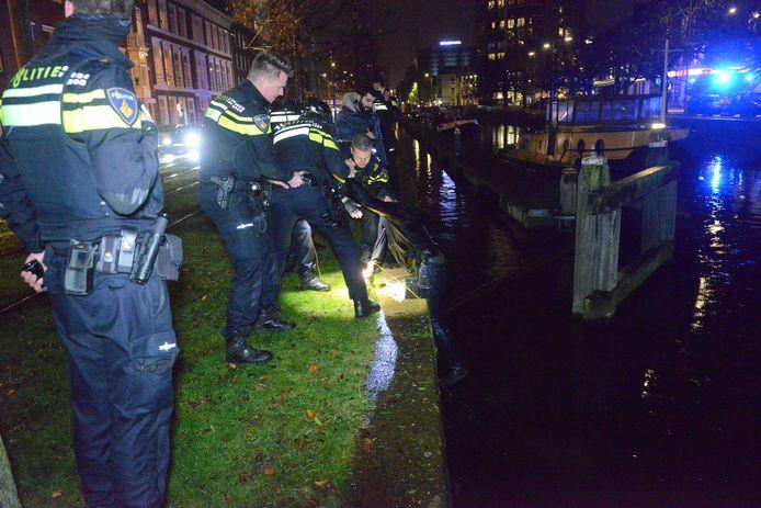De man wordt uit het water gehaald door agenten.