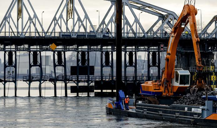 Medewerkers van Rijkswaterstaat bouwen een tijdelijke dam bij de beschadigde stuw van Grave.