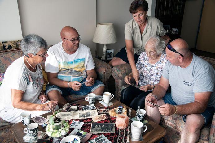 Riet Rutten, Joop Noort, Marianne Noort, Miep Janssen en Andrew Smith (vlnr) bekijken oude foto's.