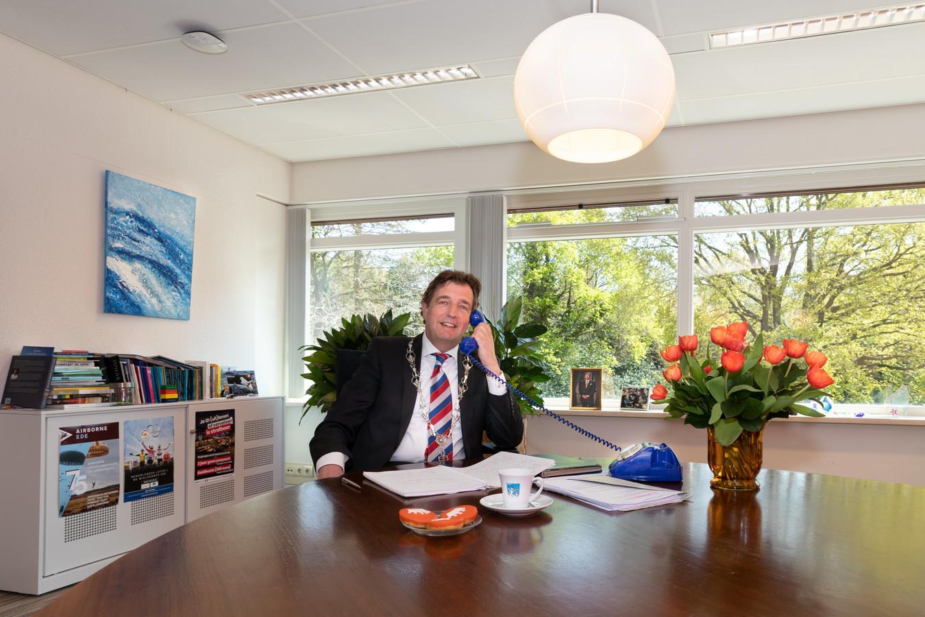Burgemeester René Verhulst van Ede belt met een van de Edenaren die een koninklijke onderscheiding krijgt.