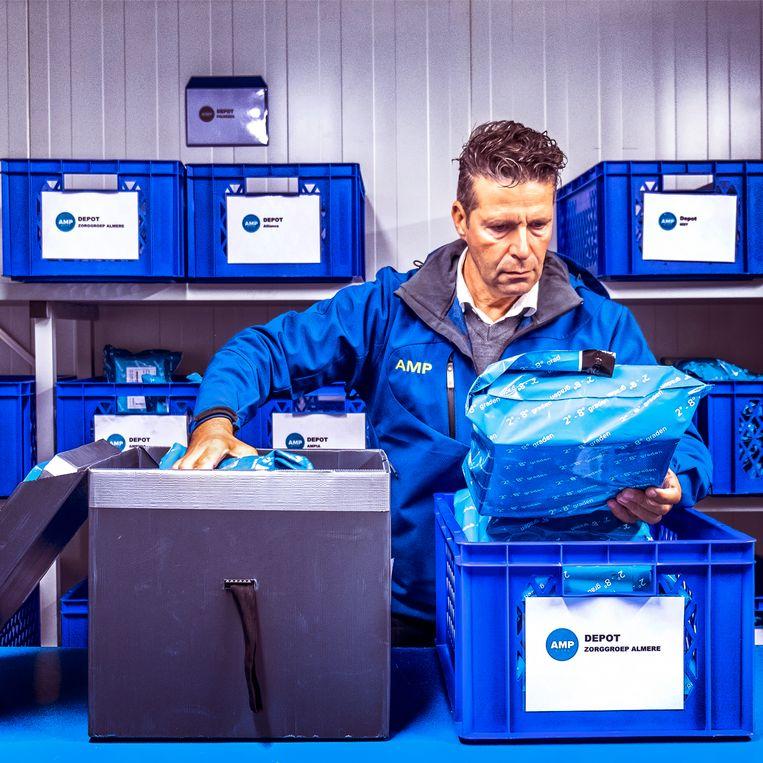 Medicijnen worden in een koelcel verpakt in een koelbox. Beeld Raymond Rutting/de Volkskrant