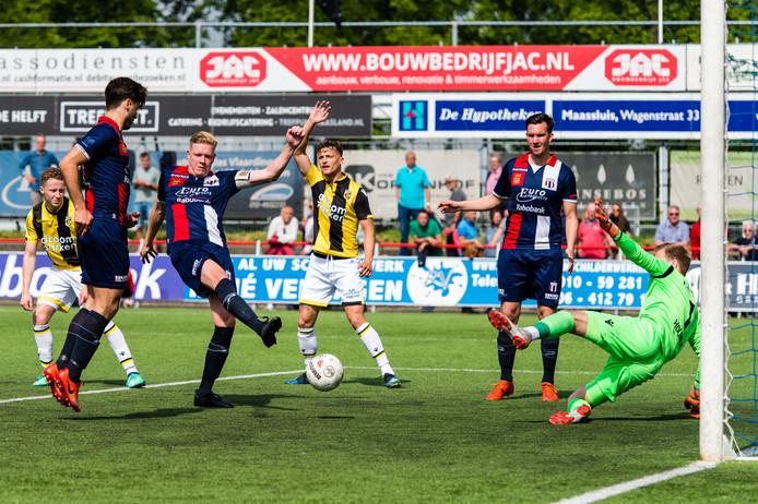 Excelsior Maassluis-speler Niels Redert passeert Jeroen Houwen, in het doel van Jong Vitesse. Ploeggenoot Mats Grotenbreg appelleert.