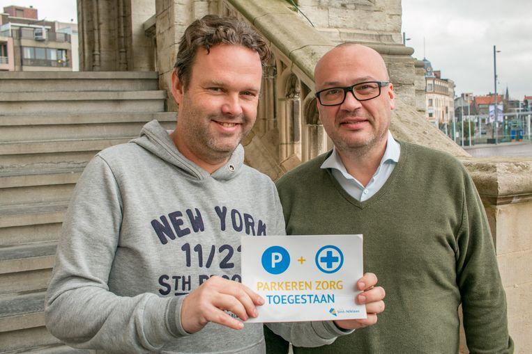 Raadslid Filip Herman en schepen Carl Hanssens met de nieuwe 'parkeren + zorg'-sticker.