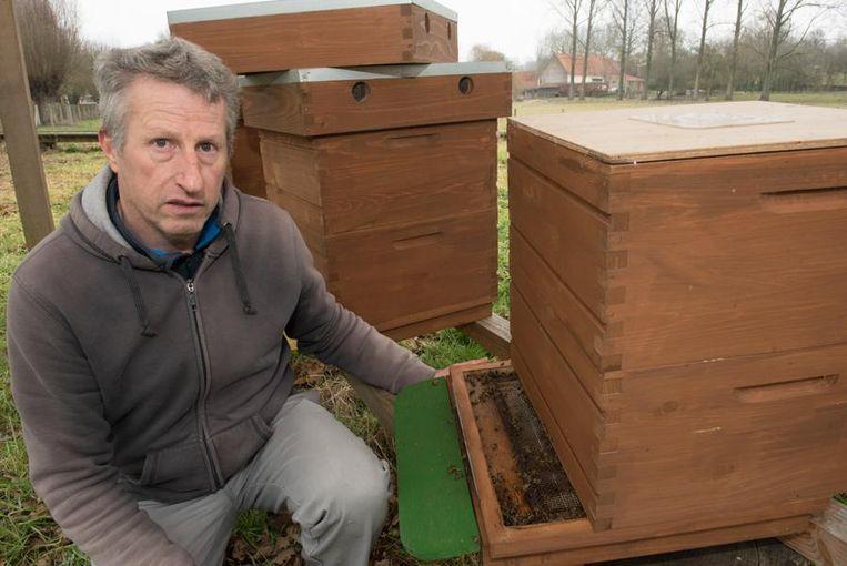 Guy Hoebeke bij de bijenkasten die hevig door elkaar geschud werden.